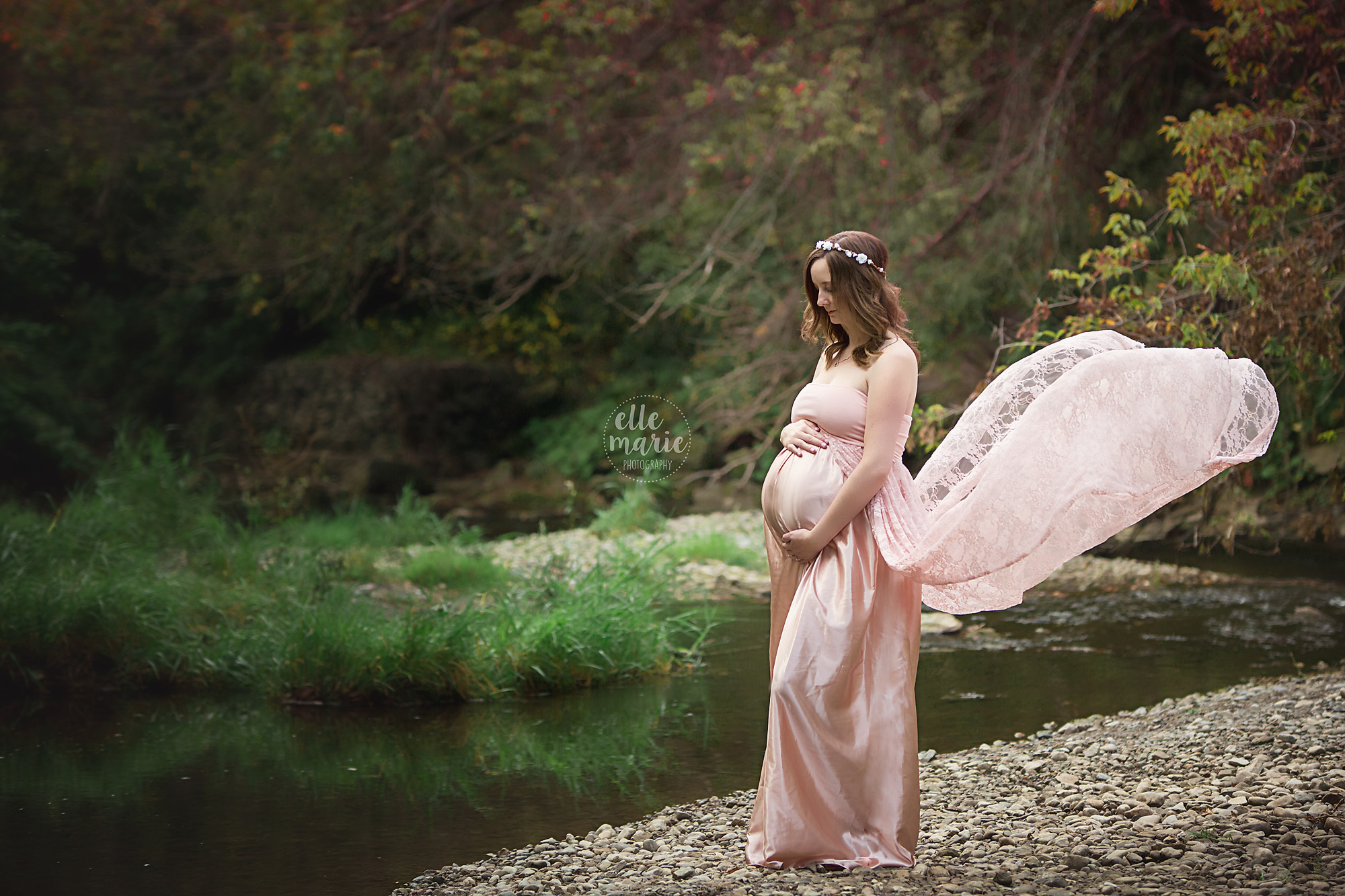 expecting mother wearing pink maternity dress blowing in the wind