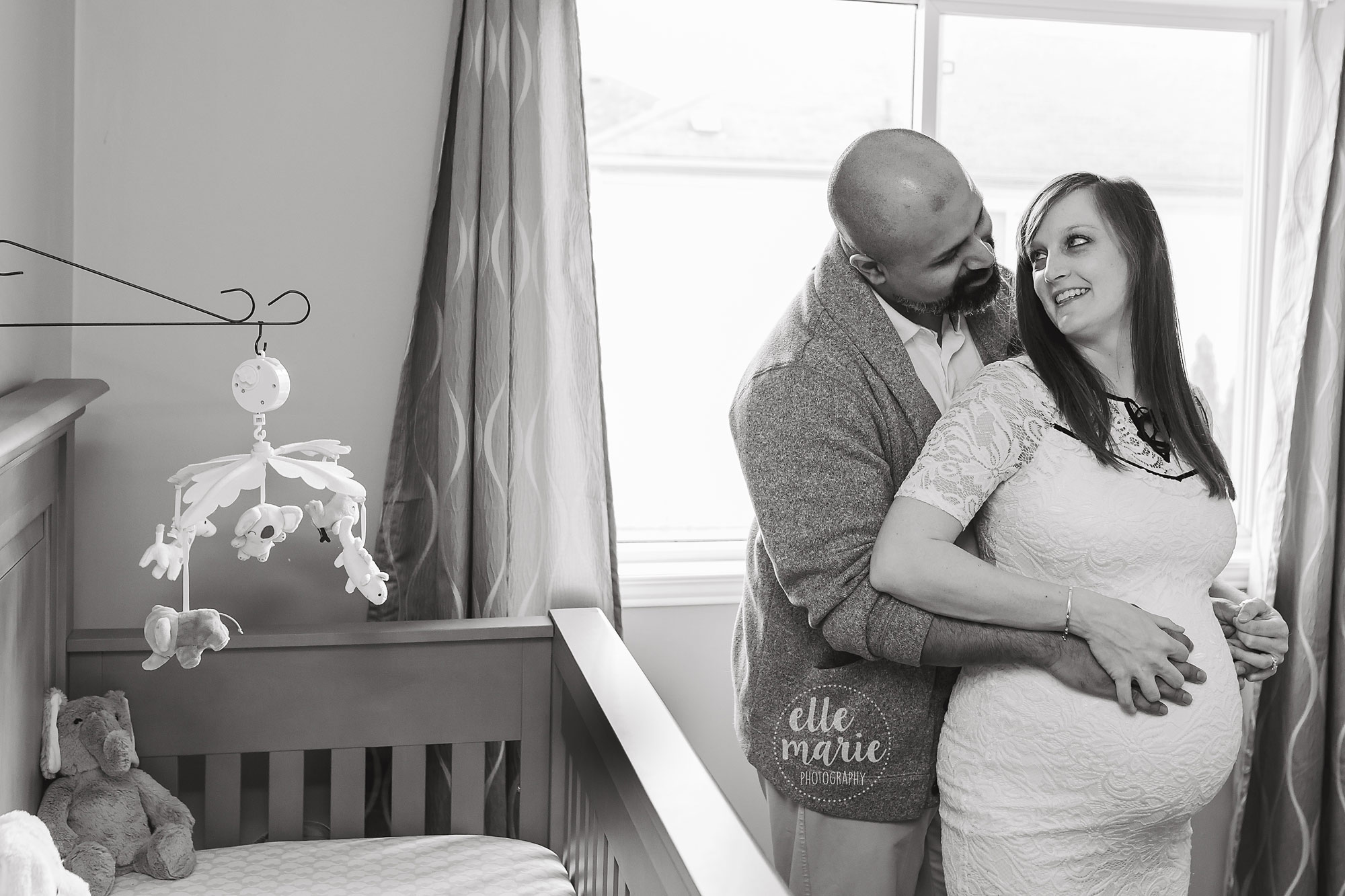 pregnant couple pose in nursery in whitby home