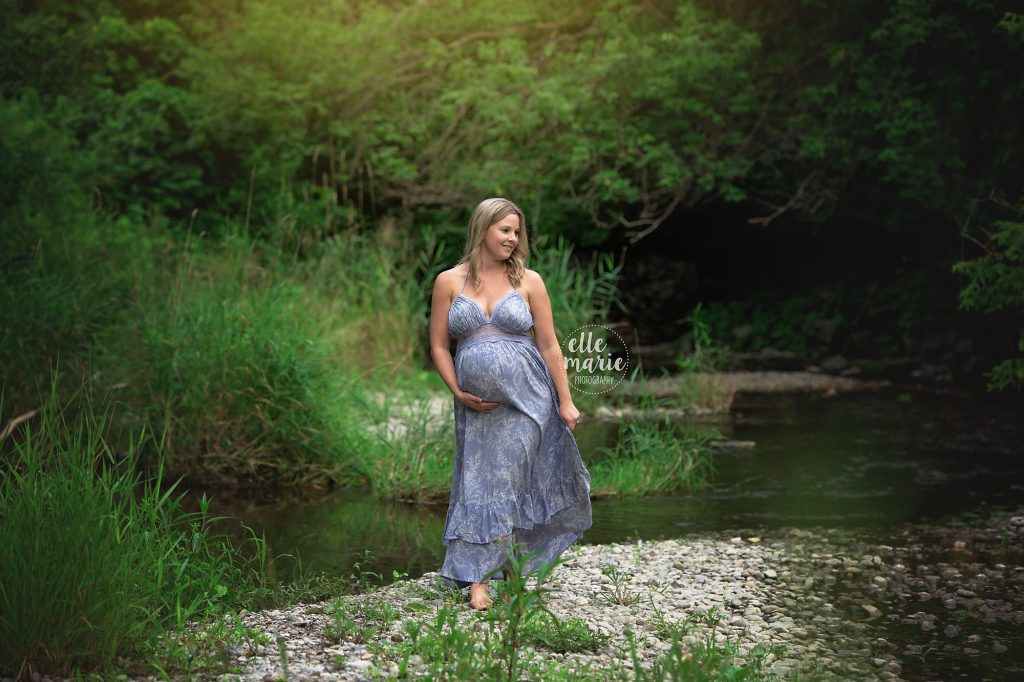 pregnant mom walks on the waterbank