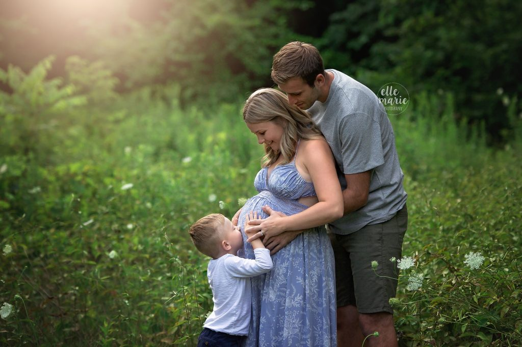 young boy kisses mom's pregnant belly while dad looks on