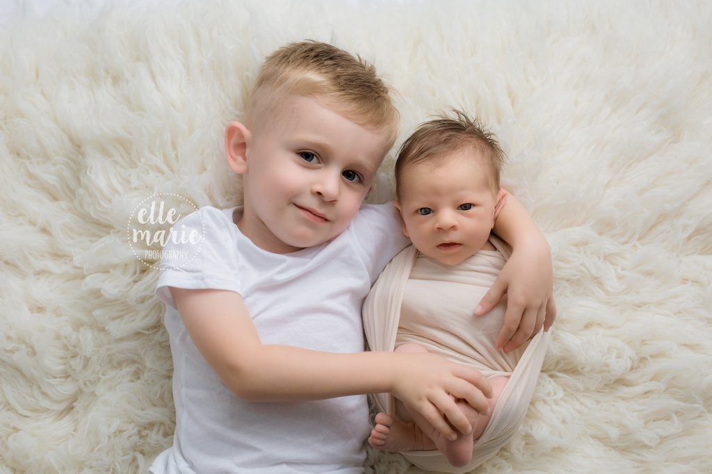 Preschool brother holding newborn sister