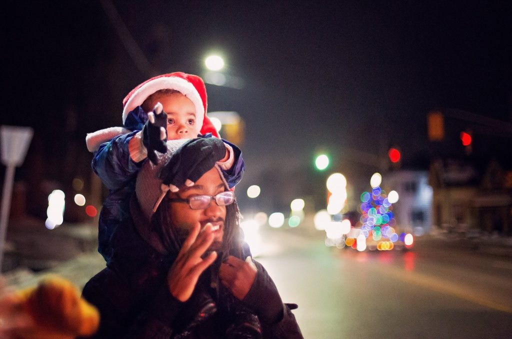 son on dad's shoulders watching Christmas Parade