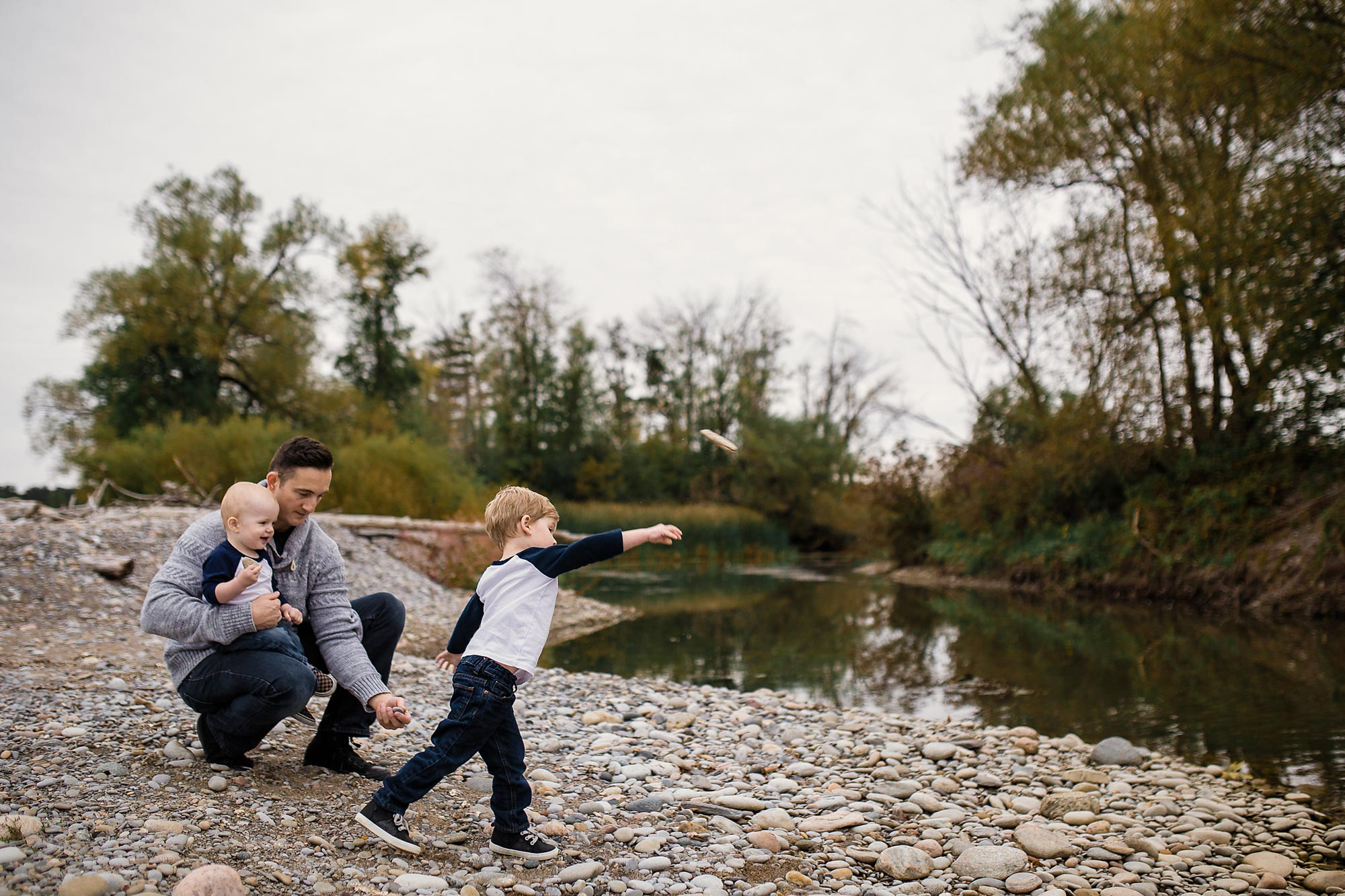 brothers throwing rocks in pond with dad