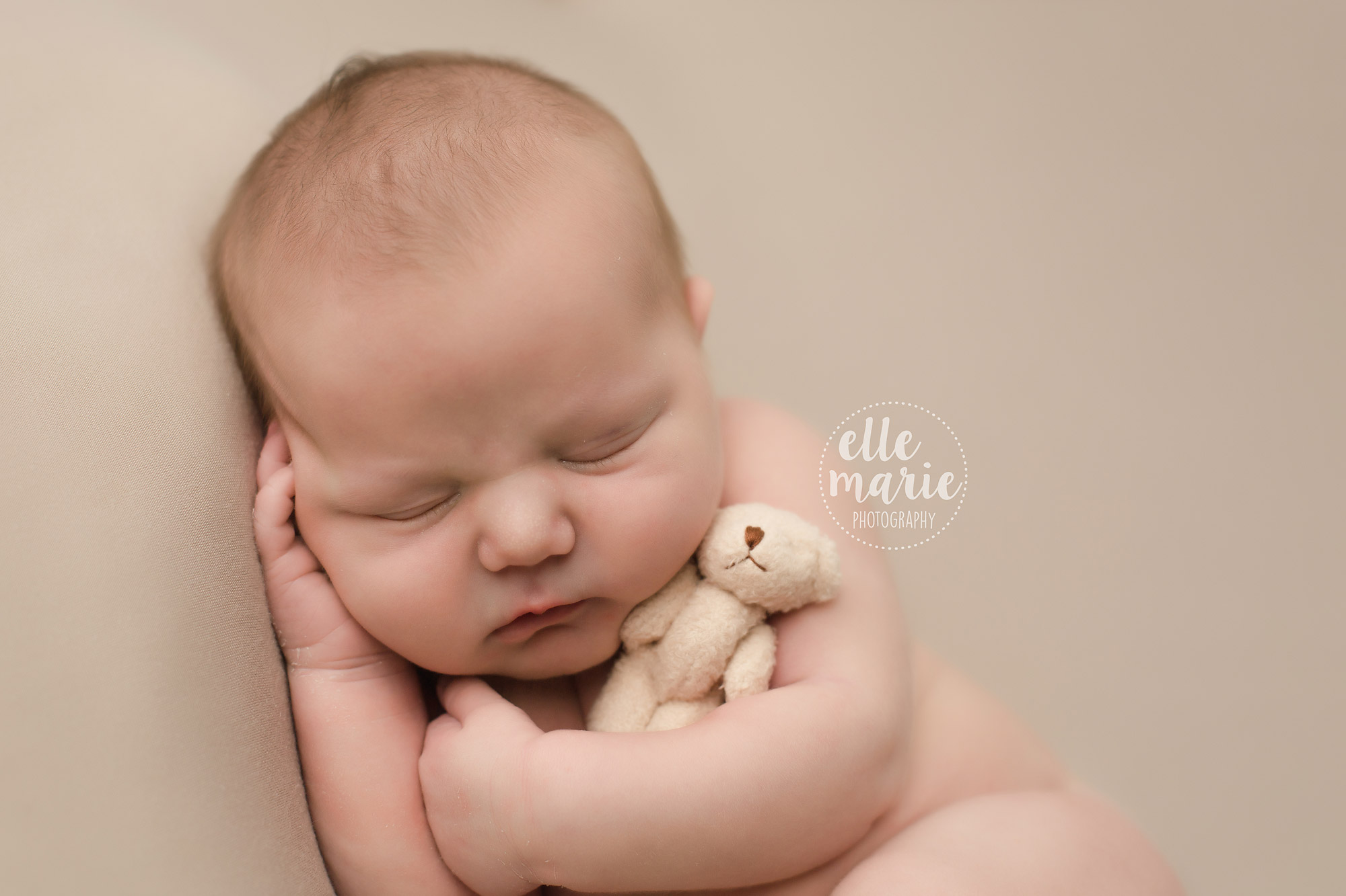 newborn baby boy hugging teddy bear