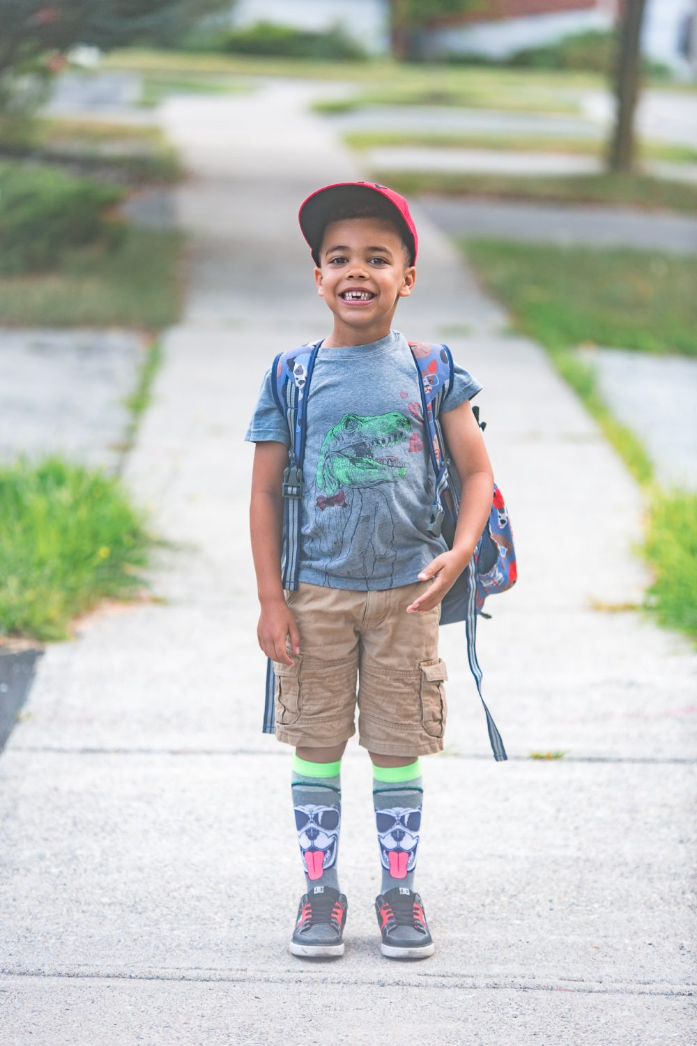 Young boy ready for first day of school, Wearing a red hat, grey shirt with a dinosaur and knee socks with a dog on them.