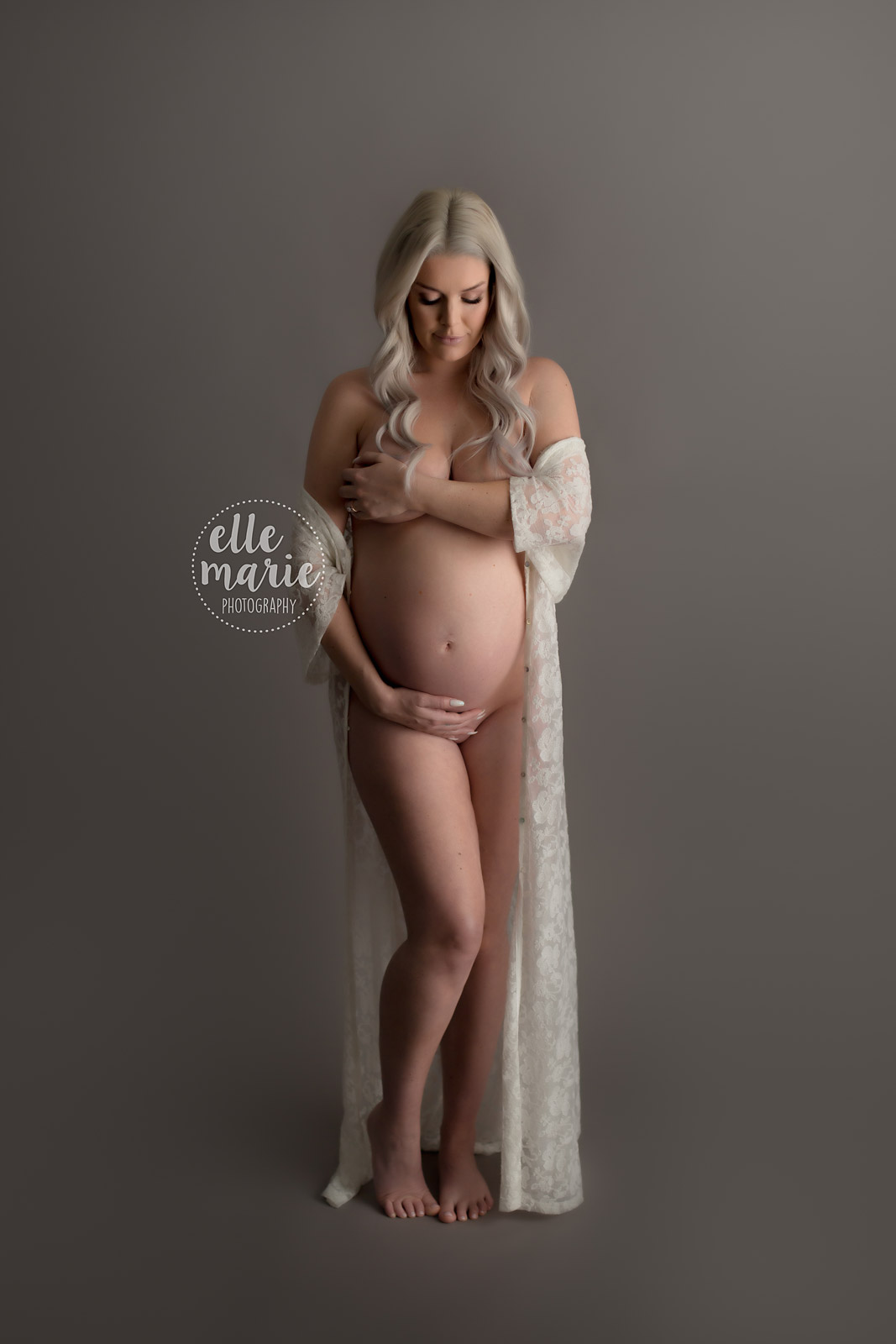 pregnant lady poses nude while hugging her belly